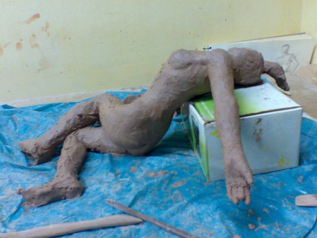 Figura humana tumbada de barro.