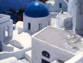 cúpula azul entre casas encaladas y mar